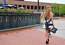 graduate poses with a rifle