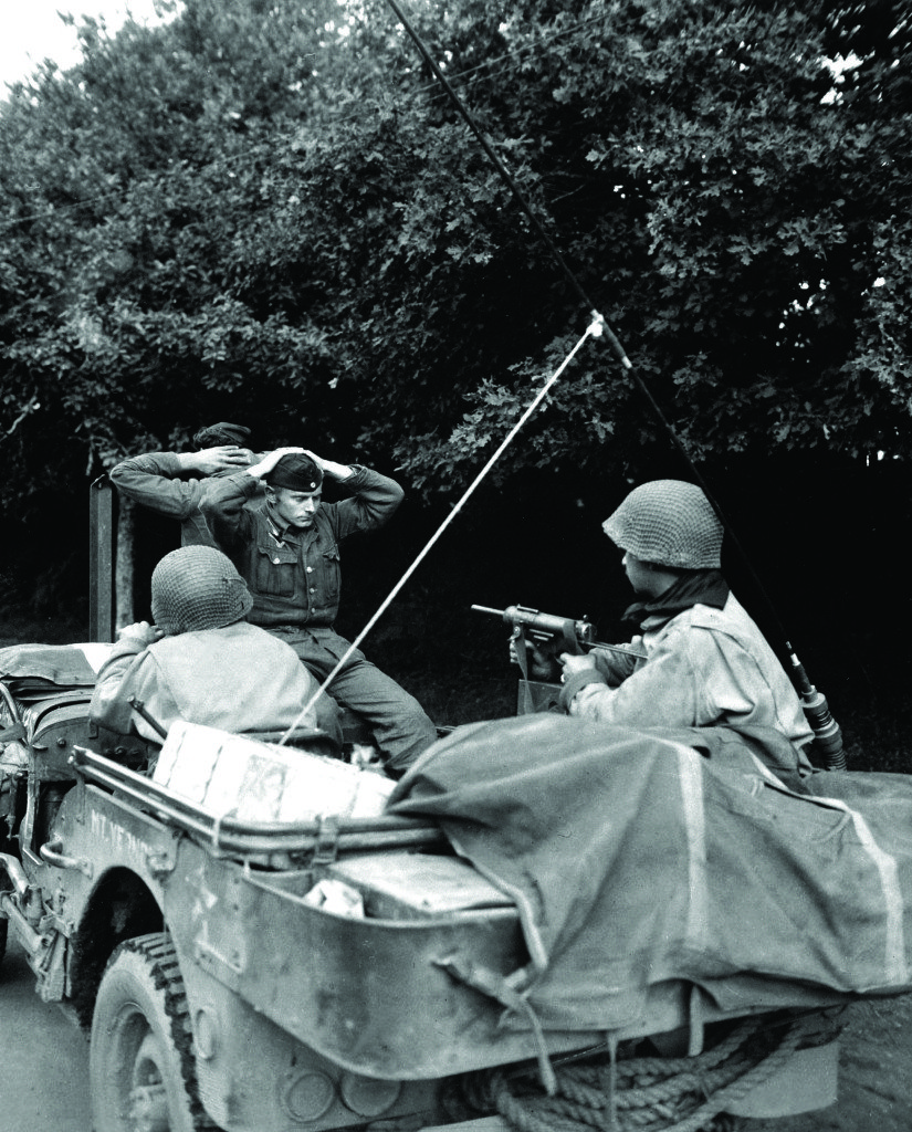 Two German prisoners of war are being taken to the 6th Div. POW Encampment for interrogation and searching.  There was 218 captured by the Free French Infantry and 6th Armored Div. troops.  Plouay, France.  August 28, 1944.  Pfc. H.M. Kuehne.  (Army) NARA FILE #:  111-SC-339075 WAR & CONFLICT BOOK #:  1284